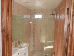 Fully tiled and featuring a walk-in monsoon shower.